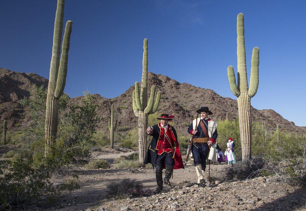 Men in historic dress in desert with saguaro cactus