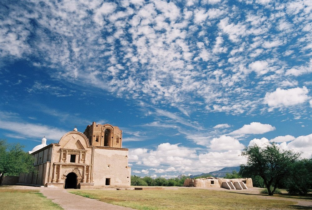 Tumacacori Mission with scattered clouds above