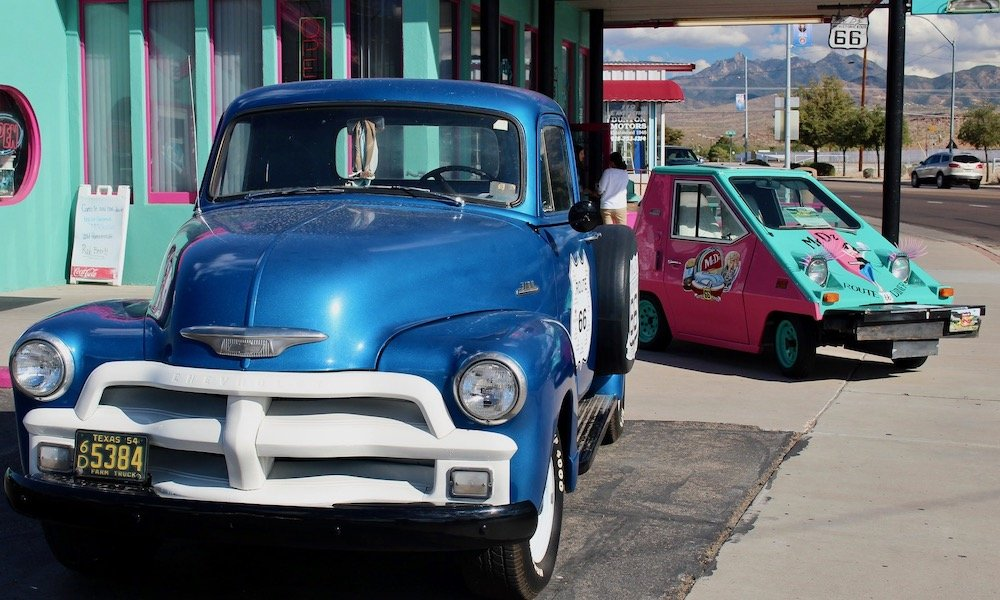 old chevy pickup, bright blue, with funny electric car in background