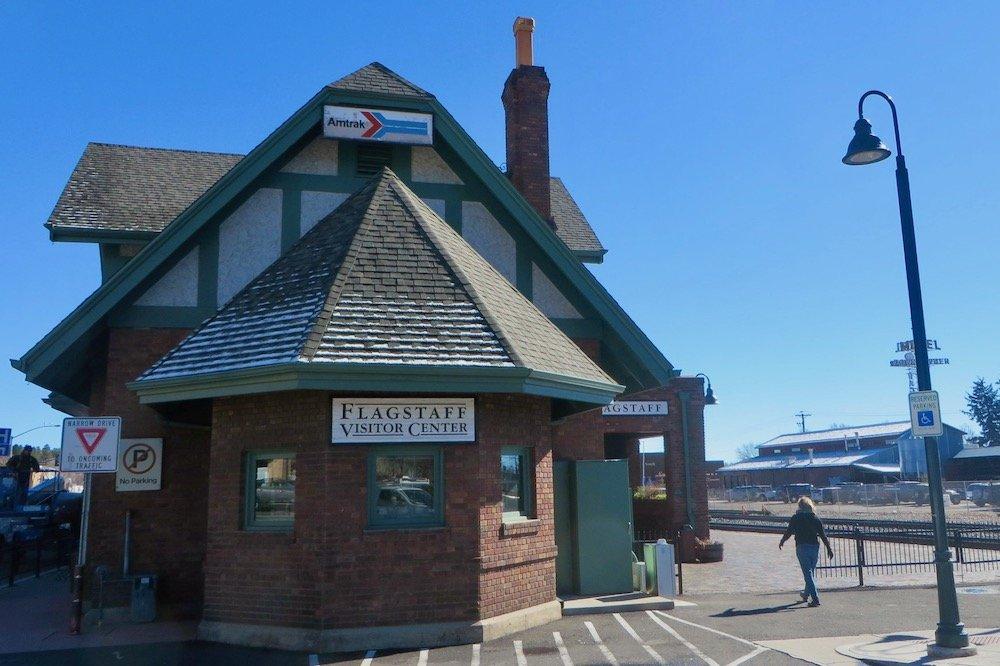 Tudor-style train station building along railroad tracks