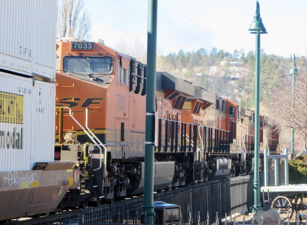 Orange freight train engines alongside teal streetlamps