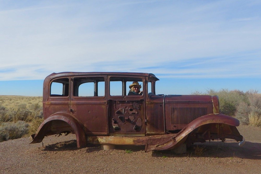 Rusted out antique car in desert