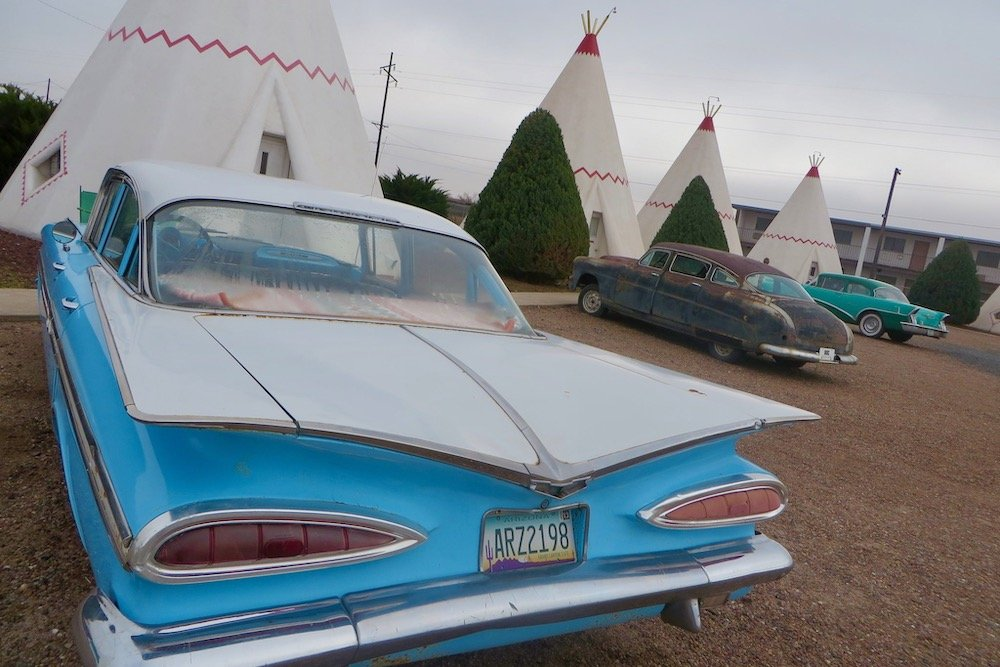 antique cars in front of kitschy teepee motel rooms route 66 holbrook arizona