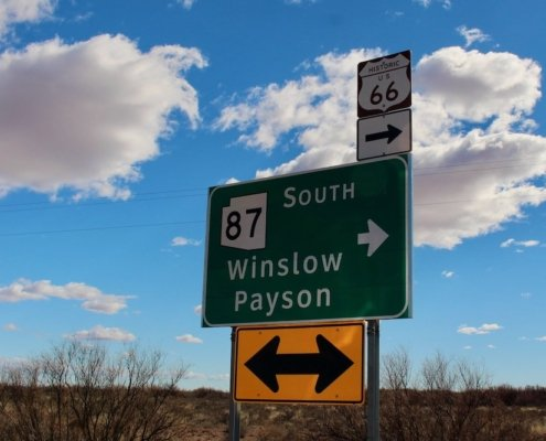 Green road sign showing directions to Payson and Winslow Arizona