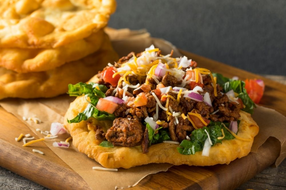 native american frybread taco, topped with meat, lettuce, tomato, cheese, onions
