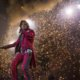 Alice Cooper in red and black striped suit, on stage with fireworks in background