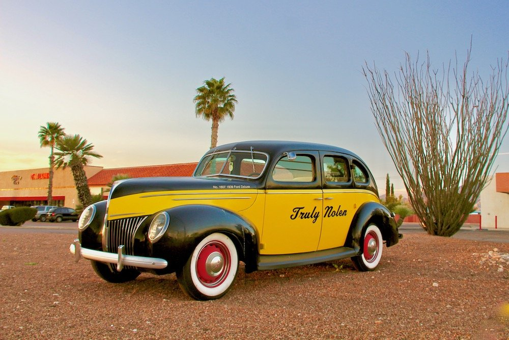 """Black and yellow antique car with the words """"Truly Nolen"""" painted on the side"""