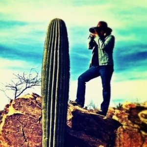 Woman in hat standing on a rock photographing a cactus, travel in arizona