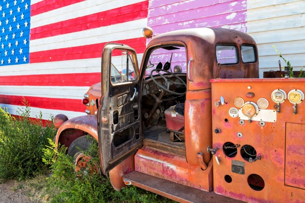 Battered old red tow truck parked in front of building with American Flag painted on side