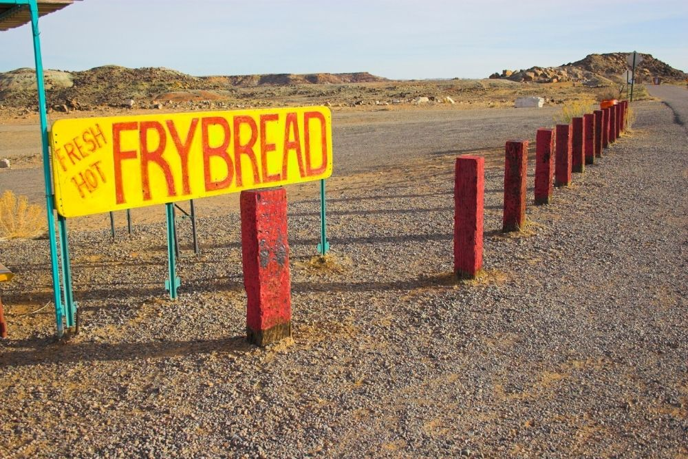 """yellow and red sign with """"frybread"""" written on it, roadway in the distance"""