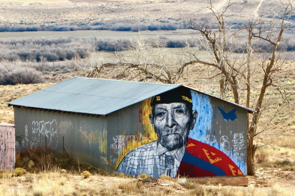 mural of a WWII Navajo code talker on the side of a barn in the Arizona desert