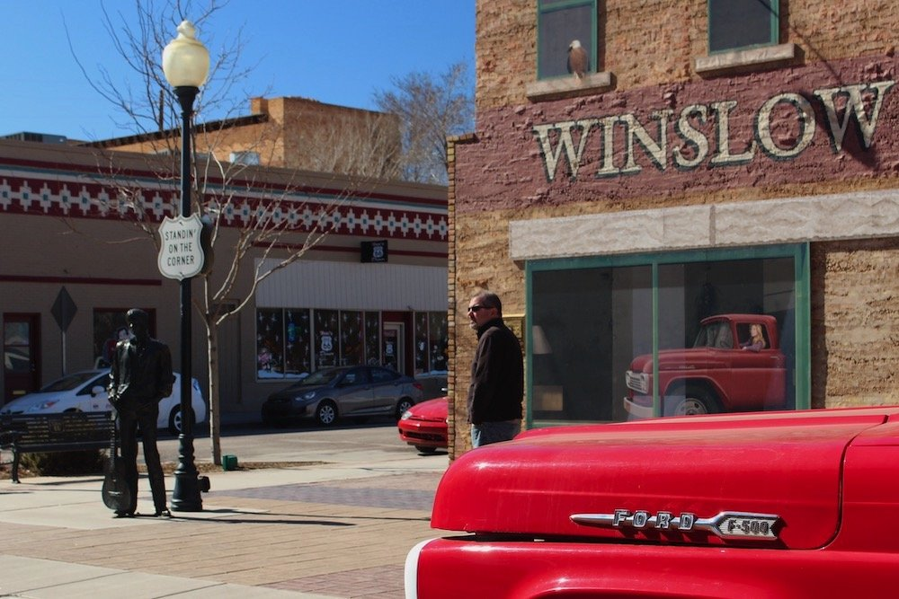 Statue of folk singer with front of ford pickup in foreground, Winslow Arizona route 66