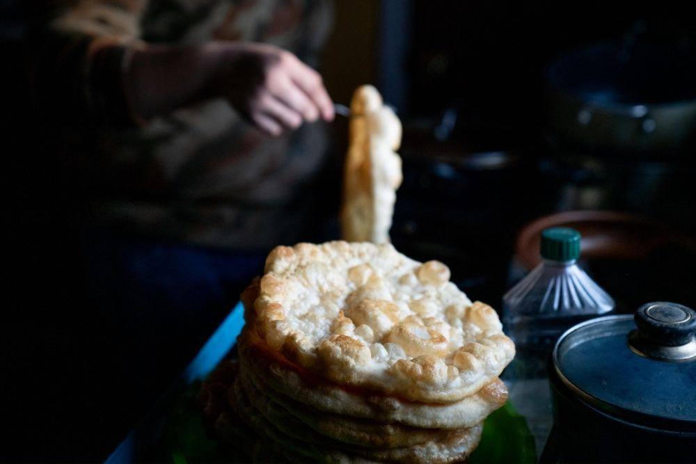 bubbly native american frybread in foreground, with woman's hand turning frybread in background