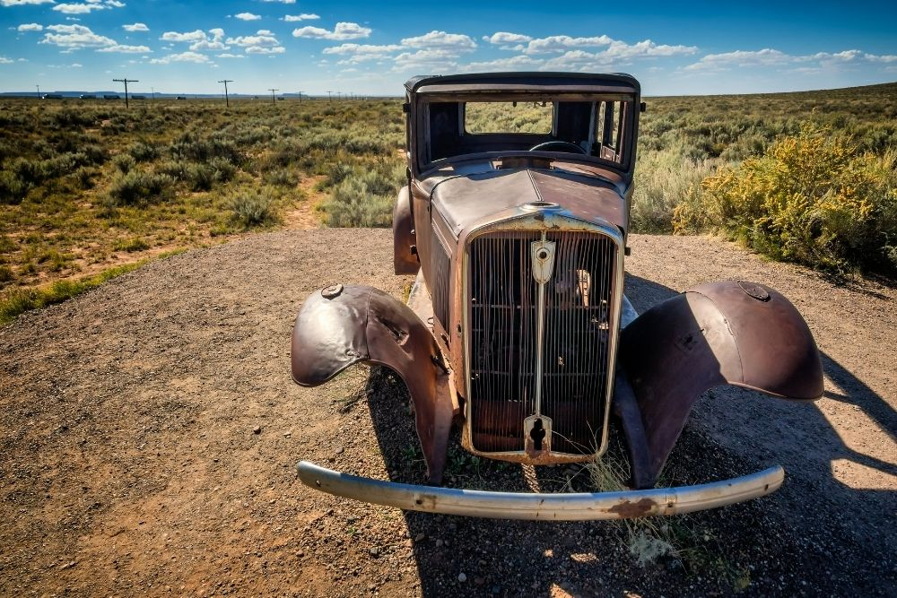 Rusty car in the middle of desert-road trip through Arizona