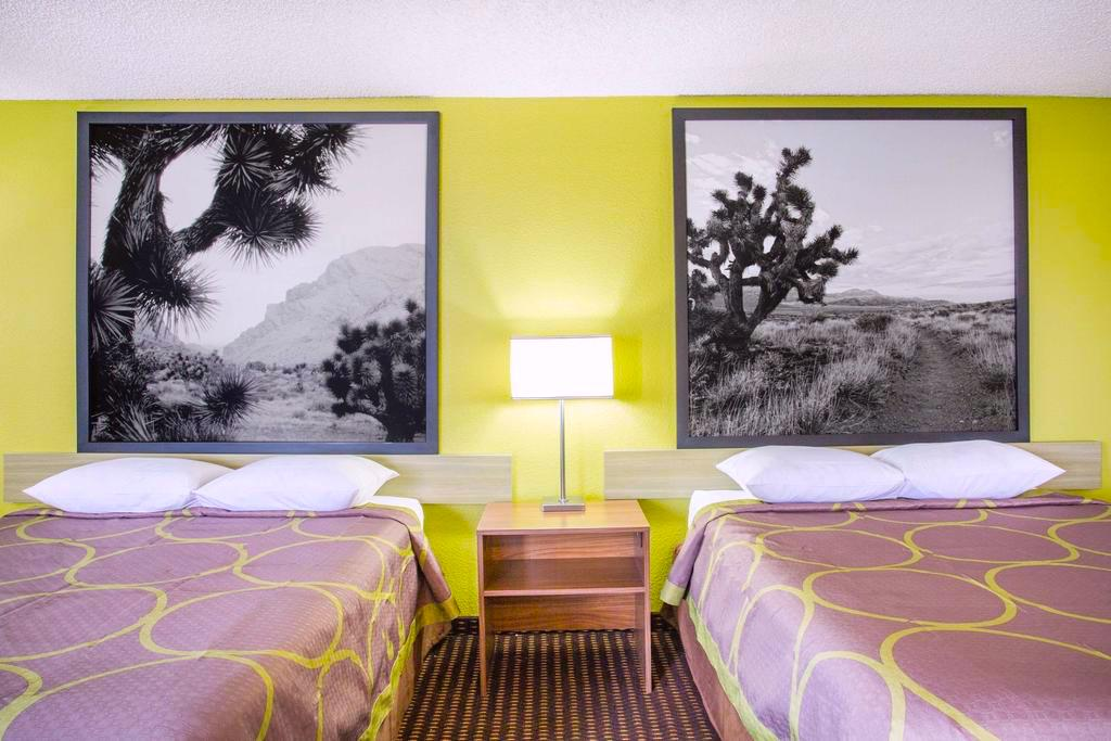 Hotel with 2 double beds, bright yellow walls, large black & white desert murals above beds, route 66 Arizona