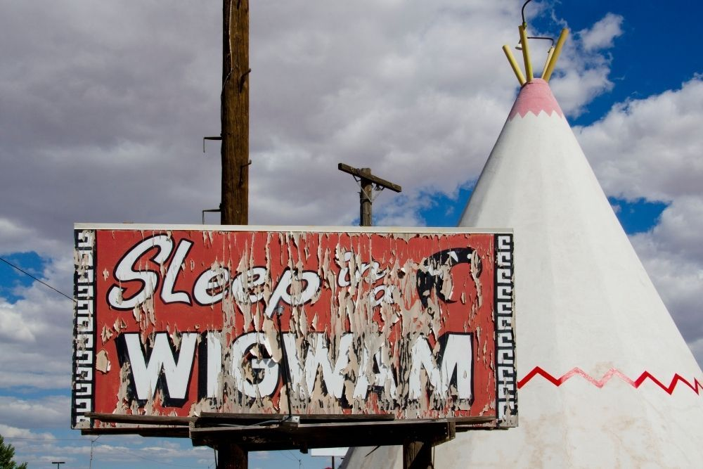 """Paint peeling on """"Sleep in a Wigwam"""" sign with concrete teepee in background route 66 in Arizona"""