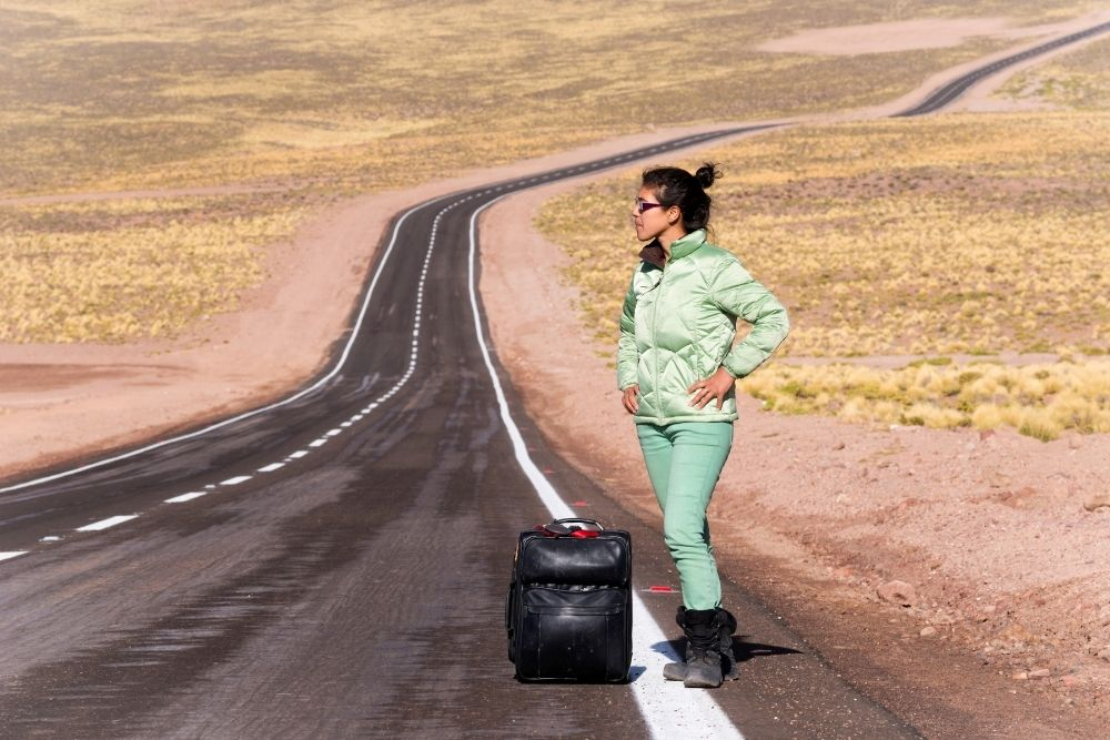 Woman stranded on the side of a desert road with a suitcase-scams on airbnb