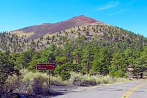 Arizona National Monuments-sign for Sunset Crater Volcano with cinder cone in background