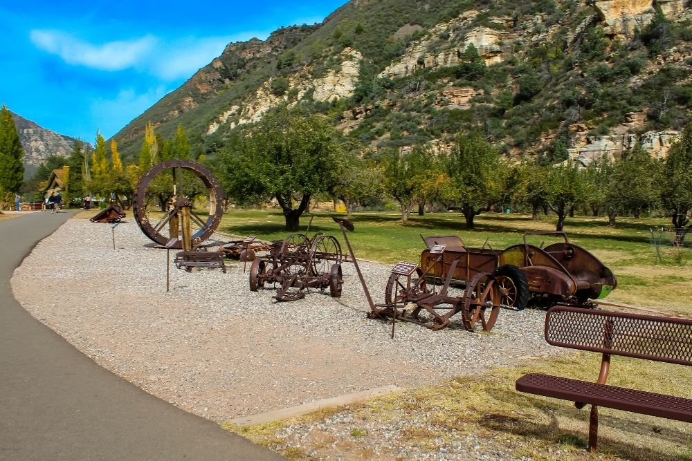 historic, rusty farm equipment in front of Pendley orchards at slide rock state park