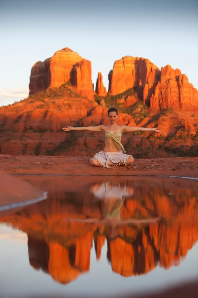 woman sitting in front of water doing yoga with red rocks in background-Sedona in fall