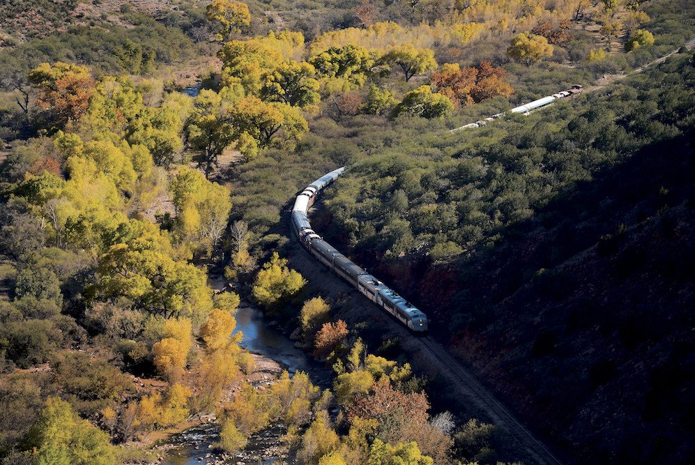 Aerial shot of Verde Canyon Railroad going through canyon along a river with trees displaying fall foliage-near Sedona in fall