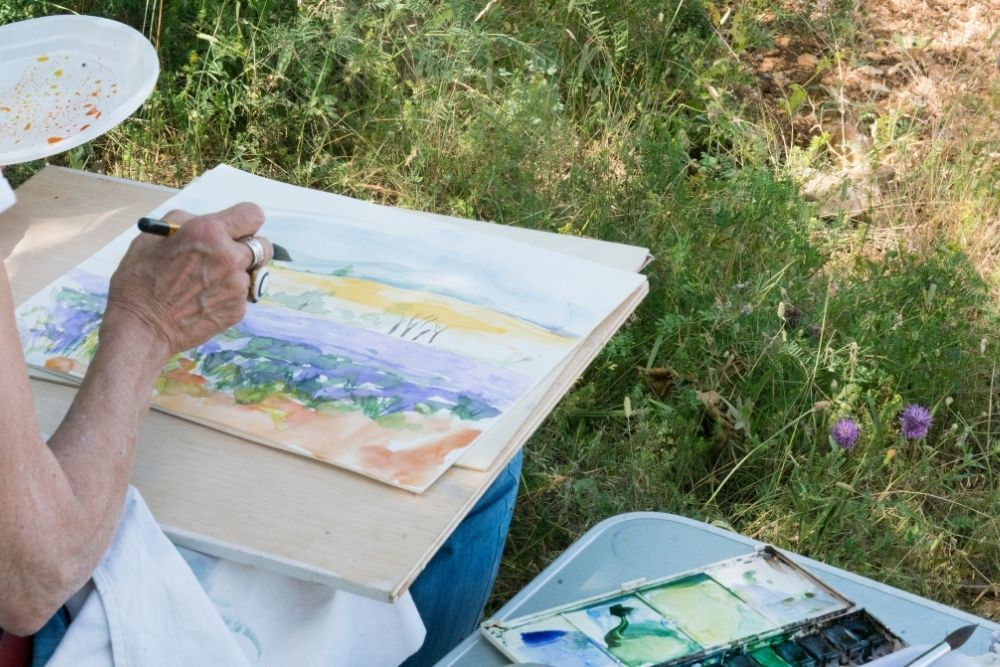 hands of artist painting a watercolor outdoors